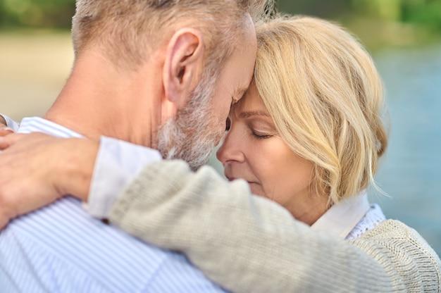 Rosto de close-up abraçando um homem e uma mulher