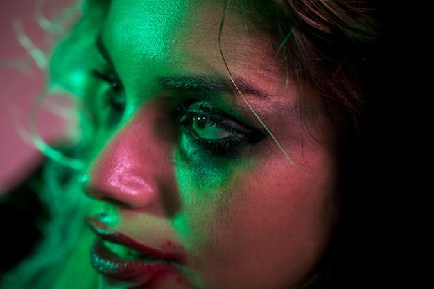 Rosto de close-up de uma mulher de maquiagem com olhos verdes
