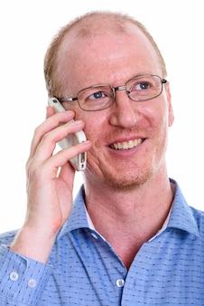 Rosto de empresário feliz sorrindo enquanto fala no celular e pensa