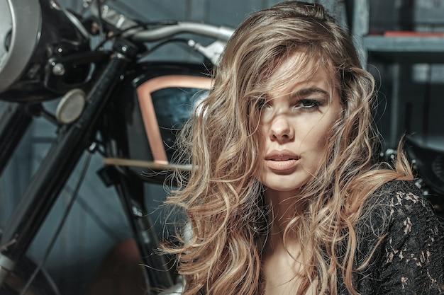 Rosto de garota sexy de mulher sensual sentado perto de uma motocicleta na superfície da garagem.