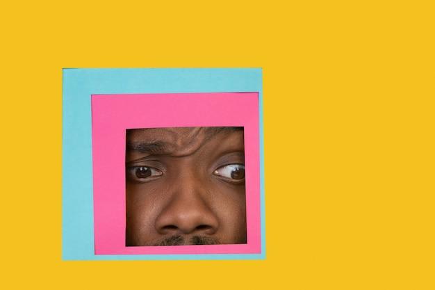 Rosto de homem afro-americano espiando através do quadrado em fundo amarelo