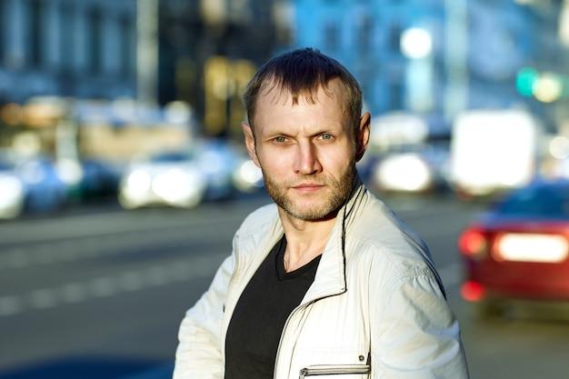 Rosto de homem barbudo sério sobre no fundo de uma rua da cidade