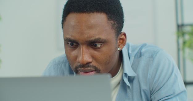 Rosto de homem bonito africano navegando na internet conversando, uso laptop em casa, freelancer, trabalhando remotamente, olhando para a tela do computador pc