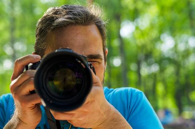 Rosto de homem coberto com lentes de câmera. jovem segurando a câmera e tiro