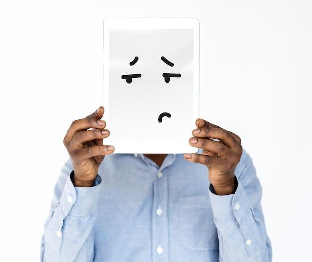 Rosto de homem coberto com tablet digital