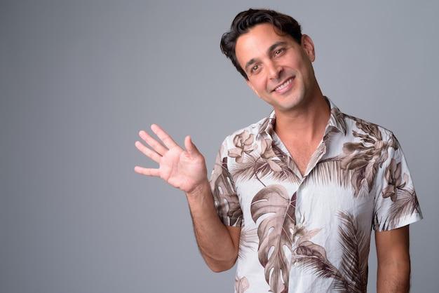 Rosto de homem feliz bonito turista hispânico acenando com a mão