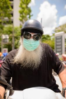 Rosto de homem maduro barbudo hipster com óculos de sol e máscara de andar de moto