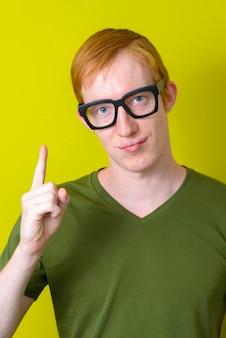 Rosto de homem nerd com cabelo ruivo, usando óculos e apontando para cima