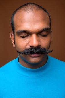 Rosto de indiano com bigode e suéter azul
