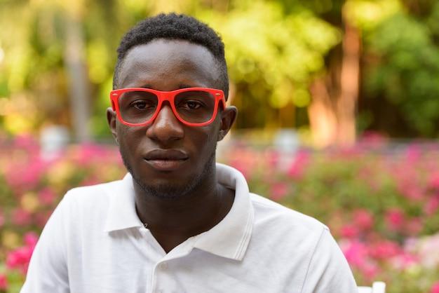 Rosto de jovem africano com óculos no parque ao ar livre