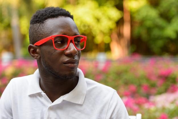 Rosto de jovem africano com óculos pensando no parque ao ar livre