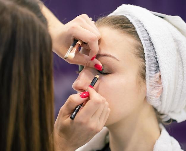 Rosto de jovem e maquiador com pincéis nas mãos dela está aplicando maquiagem