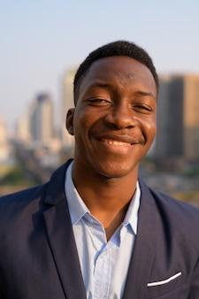 Rosto de jovem empresário africano feliz sorrindo contra a vista da cidade