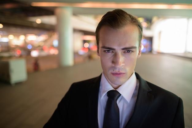 Rosto de jovem empresário ao ar livre à noite