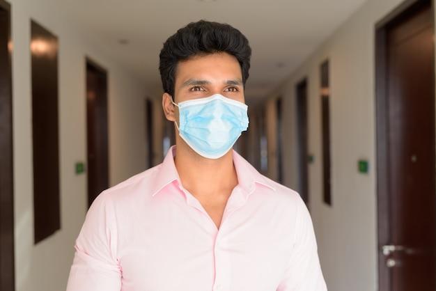 Rosto de jovem empresário indiano usando máscara e pensando no corredor