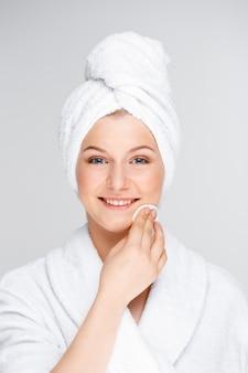 Rosto de limpeza jovem mulher após maquiagem