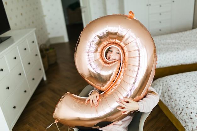 Rosto de menina bonita jovem aniversário através do buraco no balão