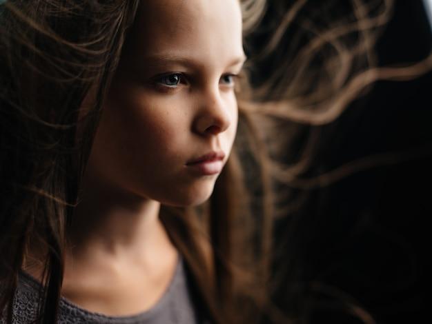 Rosto de menina com cabelo solto close-up olhar triste