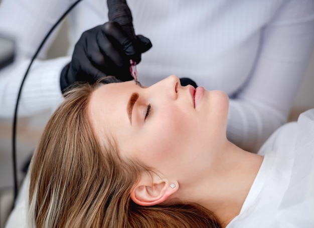 Rosto de menina de perfil durante o processo de maquiagem definitiva com microblading
