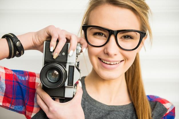 Rosto de menina na moda em óculos de sol com câmera vintage.