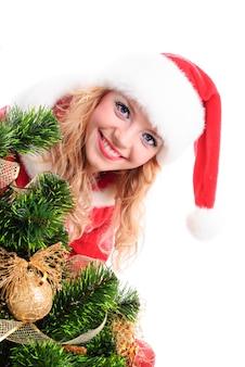 Rosto de menina santa de natal atrás de um pinheiro decorado.