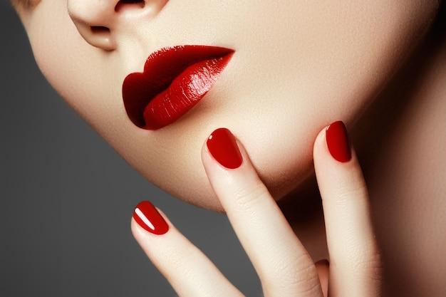 Rosto de modelo de moda de beleza. mão bem cuidada com unhas vermelhas