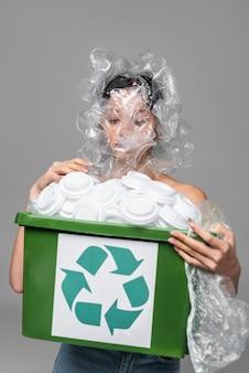 Rosto de mulher asiática coberto de copos plásticos e segurando uma lixeira