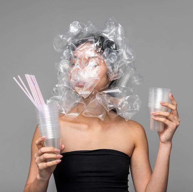 Rosto de mulher asiática sendo coberto por copos de plástico enquanto segura outros objetos de plástico