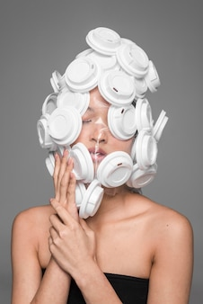 Rosto de mulher asiática sendo coberto por tampas de plástico branco