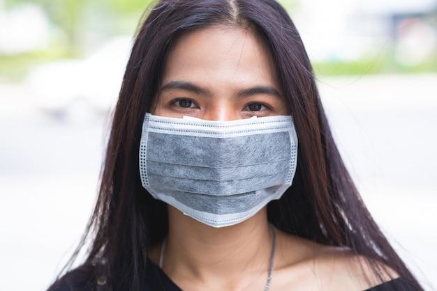 Rosto de mulher asiática usando uma máscara facial para vírus de proteção ou poluição com plano de fundo da cidade ao ar livre. coronavírus proteger.