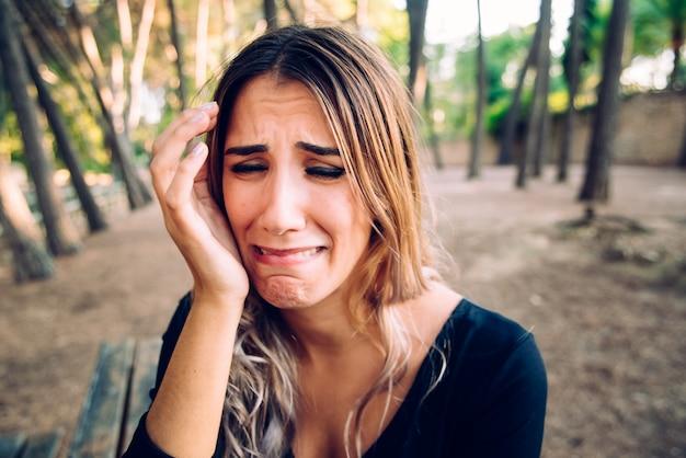 Rosto de mulher bonita chorando de nojo enquanto ela descansa a cabeça na mão.