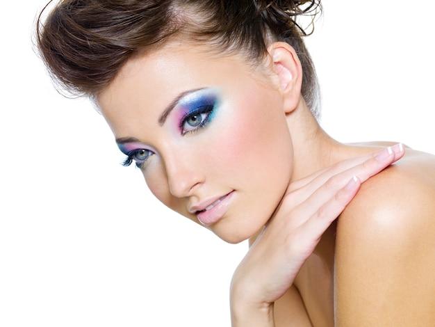 Rosto de mulher bonita com as cores de glamour da maquiagem dos olhos