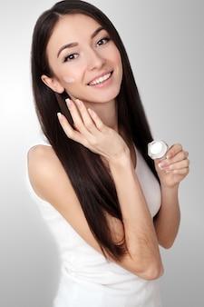 Rosto de mulher bonita com creme cosmético no rosto