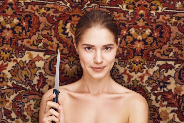 Rosto de mulher bonita com faca estúdio em fundo de carpete