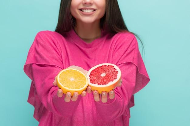 Rosto de mulher bonita com laranja suculenta