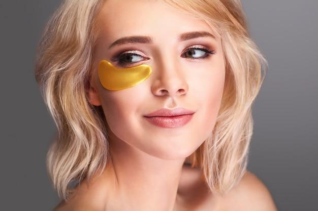 Rosto de mulher bonita com manchas de hidrogel de ouro