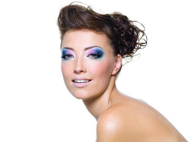 Rosto de mulher bonita com maquiagem brilhante e penteado criativo