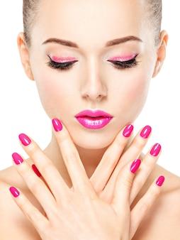 Rosto de mulher bonita com maquiagem rosa de olhos e unhas. retrato de modelo de moda glamour