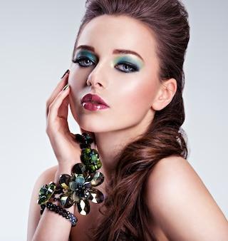 Rosto de mulher bonita com maquiagem verde fashion e joias disponíveis