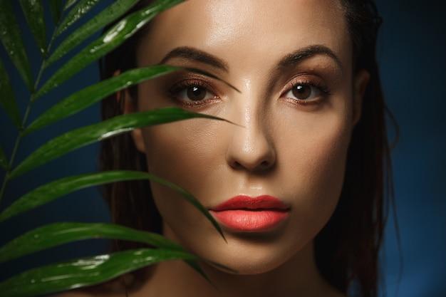 Rosto de mulher bonita com moda maquiagem na parede azul
