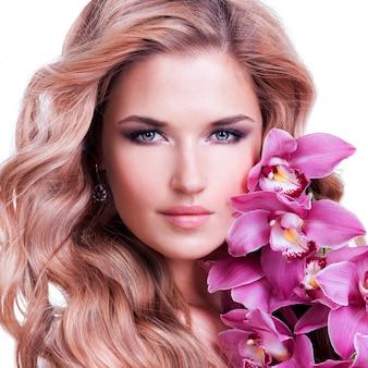 Rosto de mulher bonita com pele saudável e flor rosa sobre parede branca.