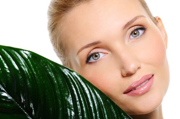 Rosto de mulher bonita e sensível com uma planta