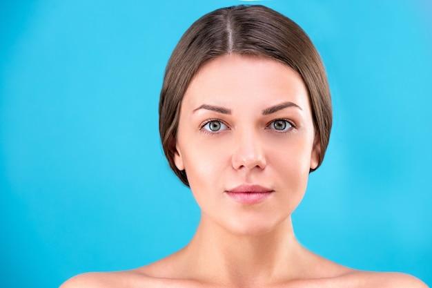 Rosto de mulher bonita. retrato da beleza da morena da jovem mulher que sorri na parede azul. pele fresca perfeita. conceito de juventude e cuidados com a pele.