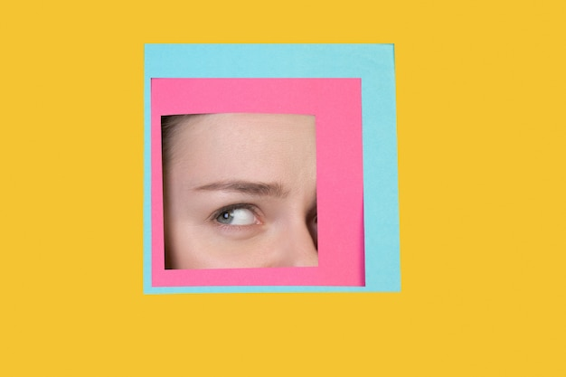 Rosto de mulher caucasiana espiando através de um quadrado em fundo amarelo