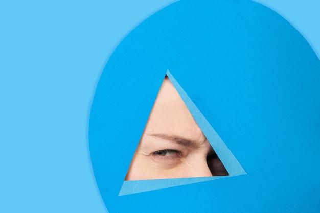 Rosto de mulher caucasiana espiando através do triângulo em fundo azul