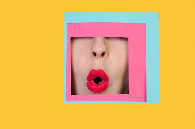 Rosto de mulher caucasiana espiando por meio de quadrado em fundo amarelo