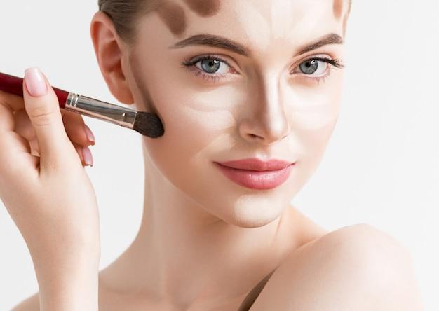 Rosto de mulher closeup. amostra de maquiagem contour highlight. contorno profissional com fundo branco