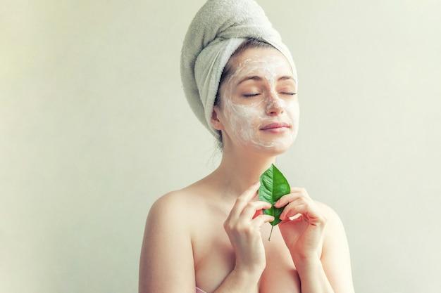 Rosto de mulher com folha verde e creme ou máscara nutritiva
