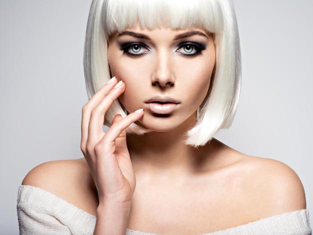 Rosto de mulher com maquiagem preta de moda de olhos e longos cílios pretos.