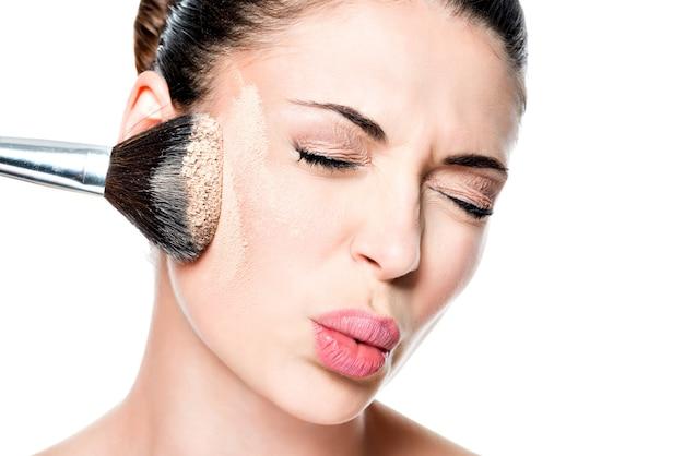 Rosto de mulher com pó na pele da bochecha